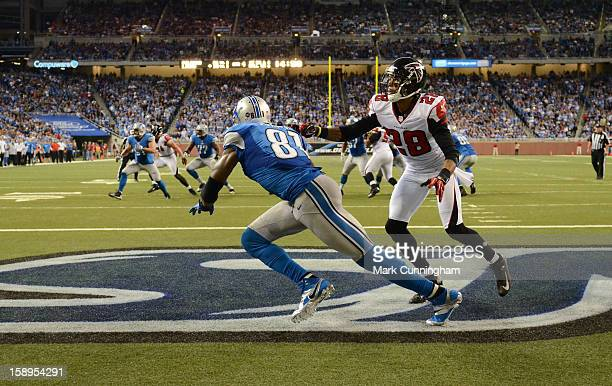 Calvin Johnson of the Detroit Lions tries to get free from Thomas DeCoud of the Atlanta Falcons during the game at Ford Field on December 22 2012 in...