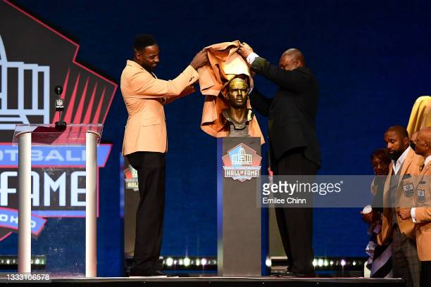 Calvin Johnson unveils his bust with Derrick Moore during the NFL Hall of Fame Enshrinement Ceremony at Tom Benson Hall Of Fame Stadium on August 08,...