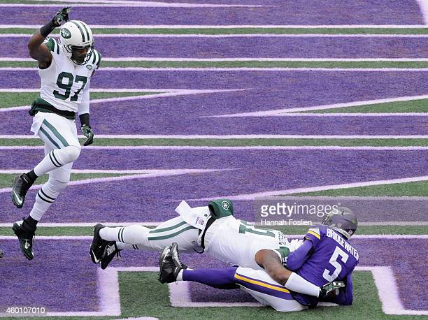 Calvin Pace of the New York Jets celebrates as teammate Sheldon Richardson sacks Teddy Bridgewater of the Minnesota Vikings in the end zone for a...