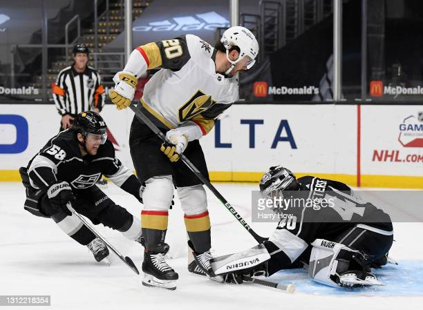 Calvin Petersen of the Los Angeles Kings makes a save on Chandler Stephenson of the Vegas Golden Knights as Kale Clague skates back during the first...