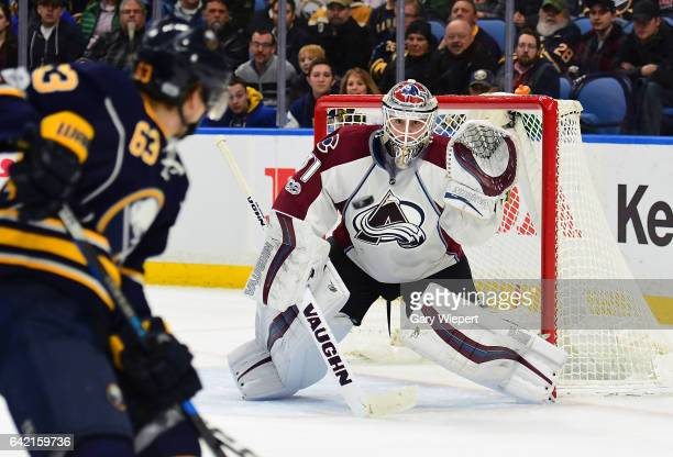 Calvin Pickard of the Colorado Avalanche eyes the puck against Tyler Ennis of the Buffalo Sabres during an NHL game at the KeyBank Center on February...