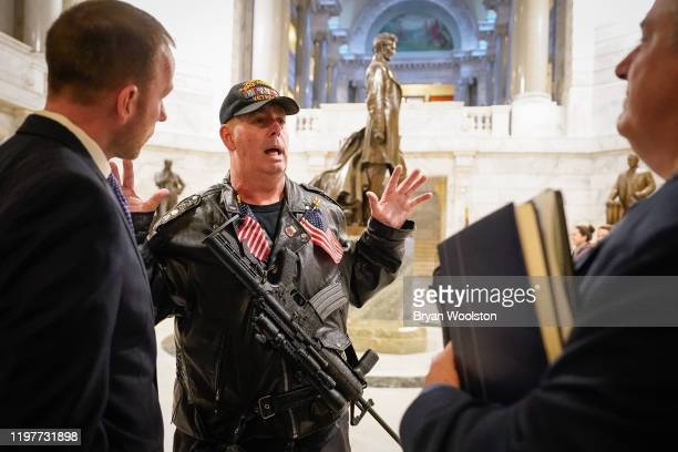 Calvin Pinkston of Louisville Ky speaks with state legislatures in the rotunda of the State Capitol while carrying a semiautoimaric rifle on January...