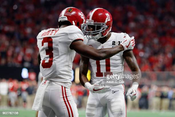 Calvin Ridley celebrates with Henry Ruggs III of the Alabama Crimson Tide after making a seven yard touchdown catch during the fourth quarter against...