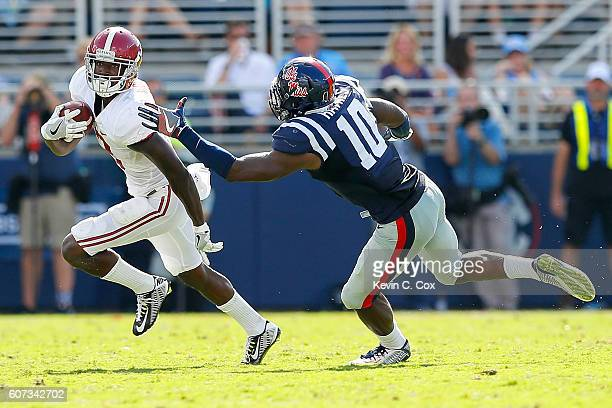 Calvin Ridley of the Alabama Crimson Tide attempts to break a tackle from Marquis Haynes of the Mississippi Rebels at VaughtHemingway Stadium on...
