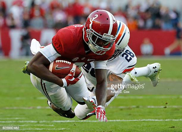 Calvin Ridley of the Alabama Crimson Tide is tackled by Tray Matthews of the Auburn Tigers at BryantDenny Stadium on November 26 2016 in Tuscaloosa...