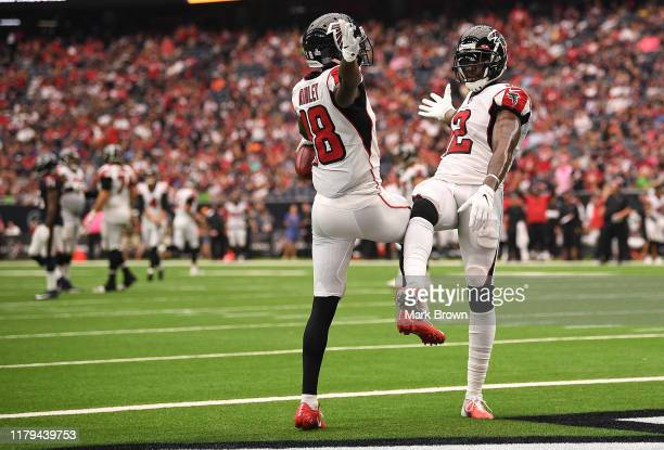 Calvin Ridley of the Atlanta Falcons celebrates with Mohamed Sanu after scoring a touchdown in the fourth quarter against the Houston Texans at NRG...
