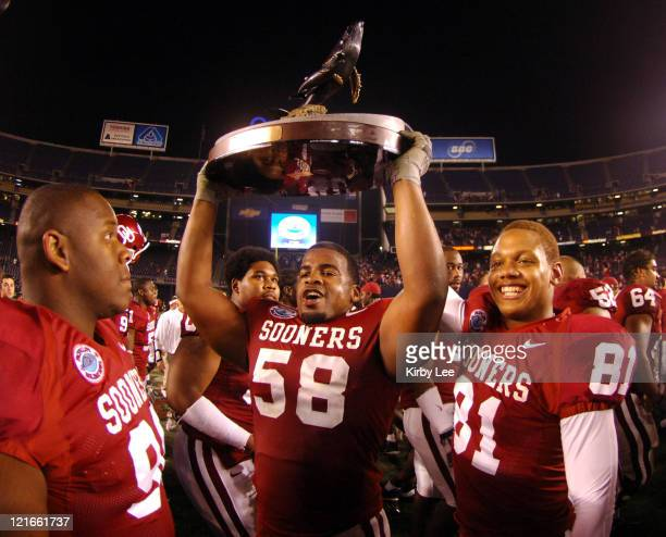 Calvin Thibodeaux and Fred Strong of Oklahoma hoist the Holiday Bowl championship trophy after 1714 victory over Oregon at Qualcomm Stadium in San...