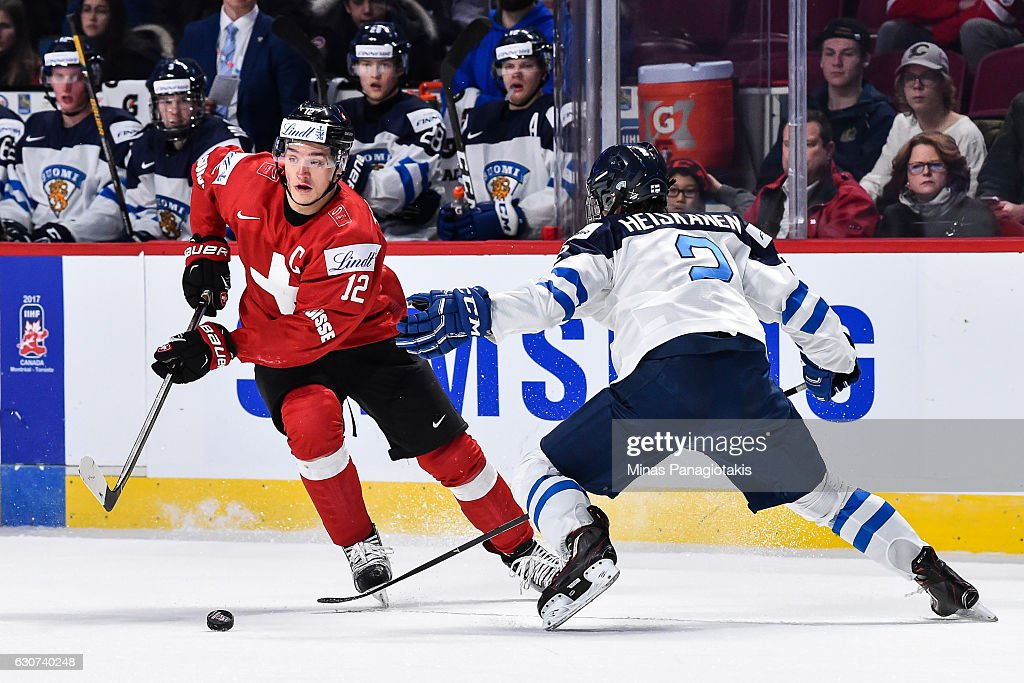 Calvin Thurkauf #12 of Team Switzerland skates the puck against Miro Heiskanen #2 of Team Finland during the 2017 IIHF World Junior Championship preliminary round game at the Bell Centre on December 31, 2016 in Montreal, Quebec, Canada. Team Finland defeated Team Switzerland 2-0.