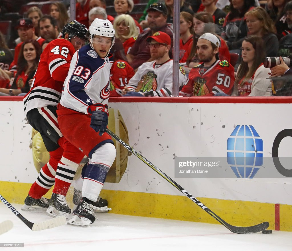 Calvin Thurkauf #83 of the Columbus Blue Jackets is pressured by Gustav Forsling #42 of the Chicago Blackhawks during a preseason game at the United Center on September 23, 2017 in Chicago, Illinois.