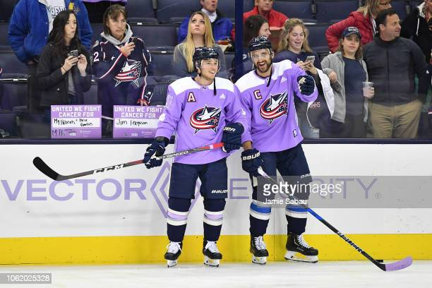 Cam Atkinson and Nick Foligno of the Columbus Blue Jackets sport purple jerseys for Hockey Fights Cancer Night during pregame warm ups prior to a...