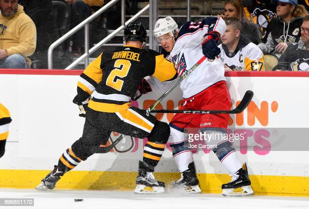 Cam Atkinson of the Columbus Blue Jackets and Chad Ruhwedel of the Pittsburgh Penguins battle at PPG Paints Arena on December 21 2017 in Pittsburgh...