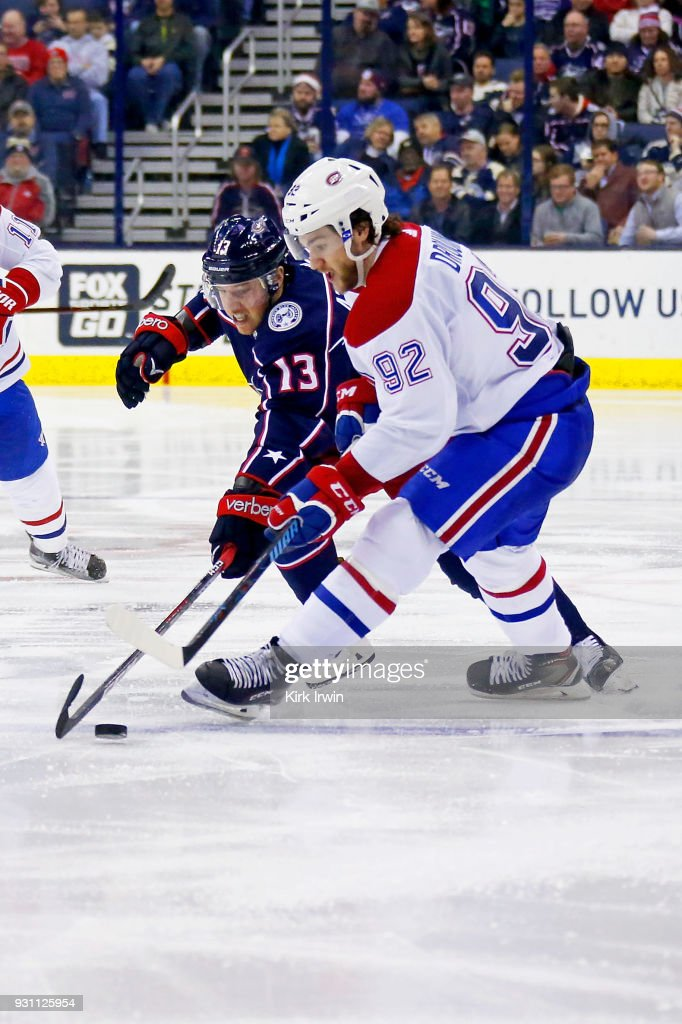 Cam Atkinson #13 of the Columbus Blue Jackets and Jonathan Drouin #92 of the Montreal Canadiens battle for control of the puck during the third period on March 12, 2018 at Nationwide Arena in Columbus, Ohio. Columbus defeated Montreal 5-2.