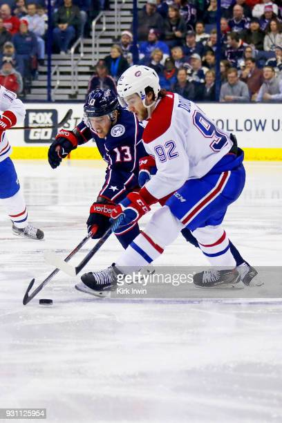 Cam Atkinson of the Columbus Blue Jackets and Jonathan Drouin of the Montreal Canadiens battle for control of the puck during the third period on...