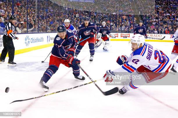 Cam Atkinson of the Columbus Blue Jackets and Kevin Shattenkirk of the New York Rangers battle for control of the puck during the first period on...