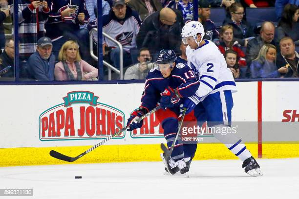Cam Atkinson of the Columbus Blue Jackets and Ron Hainsey of the Toronto Maple Leafs battle for control of the puck during the first period on...