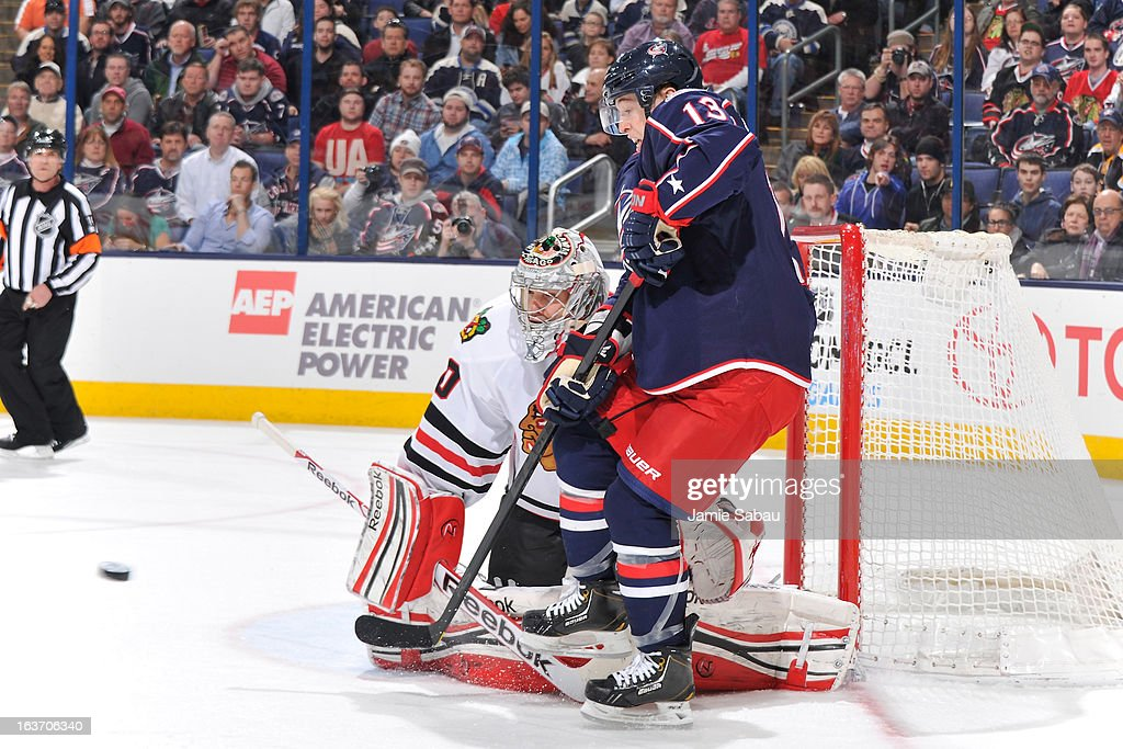 Cam Atkinson #13 of the Columbus Blue Jackets attempts to deflect the puck past goaltender Corey Crawford #50 of the Chicago Blackhawks during the third period on March 14, 2013 at Nationwide Arena in Columbus, Ohio. Chicago defeated Columbus 2-1 in a shootout.