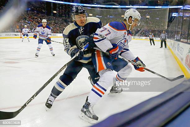 Cam Atkinson of the Columbus Blue Jackets battles for control of a loose puck against Oscar Klefbom of the Edmonton Oilers during the first period on...