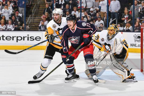 Cam Atkinson of the Columbus Blue Jackets battles for position with Justin Schultz of the Pittsburgh Penguins in front of goaltender MarcAndre Fleury...
