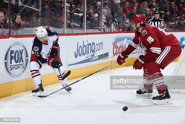 Cam Atkinson of the Columbus Blue Jackets centers the puck past Rostislav Klesla of the Phoenix Coyotes during the second period of the NHL game at...
