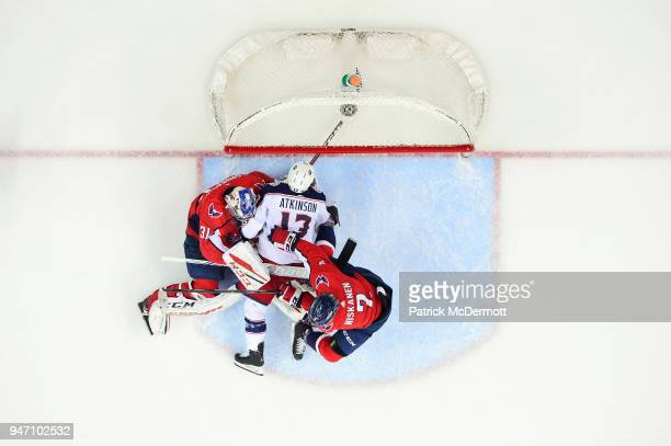 Cam Atkinson of the Columbus Blue Jackets collides with Philipp Grubauer and Matt Niskanen of the Washington Capitals in the first period in Game Two...