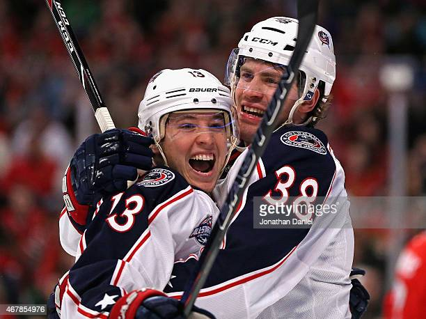 Cam Atkinson of the Columbus Blue Jackets gets a hug from teammate Boone Jenner after s coring a goal in the first period against the Chicaho...