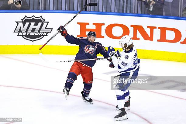 Cam Atkinson of the Columbus Blue Jackets is hit by Mikhail Sergachev of the Tampa Bay Lightning as he celebrates after scoring a goal during the...