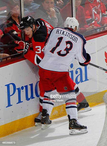 Cam Atkinson of the Columbus Blue Jackets playing in his 100th NHL game checks Jon Merrill of the New Jersey Devils against the boards during the...
