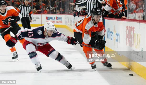 Cam Atkinson of the Columbus Blue Jackets reaches with his stick to prevent Jordan Weal of the Philadelphia Flyers from reaching the loose puck along...