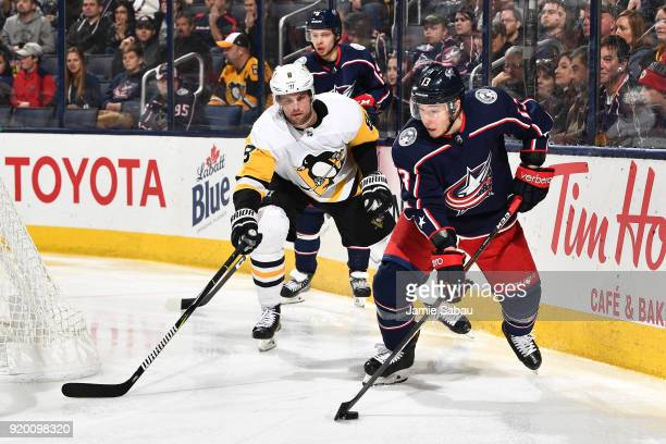 Cam Atkinson of the Columbus Blue Jackets skates the puck away from Brian Dumoulin of the Pittsburgh Penguins during the third period of a game on...
