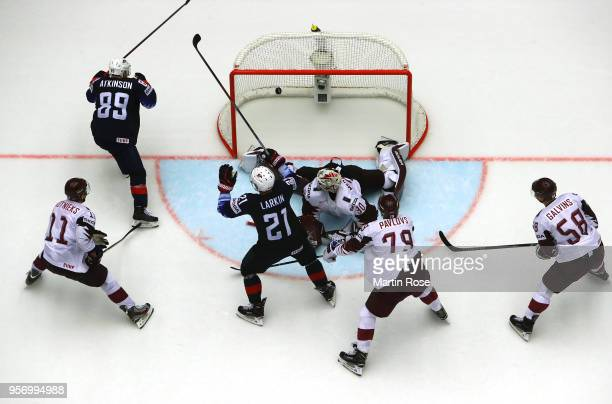 Cam Atkinson of United States scores the game winning goal in over time over Elvis Merzlikins goaltender of Latvia during the 2018 IIHF Ice Hockey...