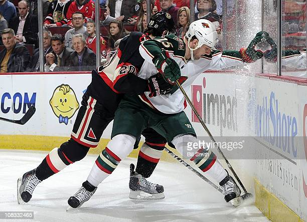 Cam Barker of the Minnesota Wild works to get the puck from the boards while being pushed by Jack Skille of the Chicago Blackhawks on January 25 2011...