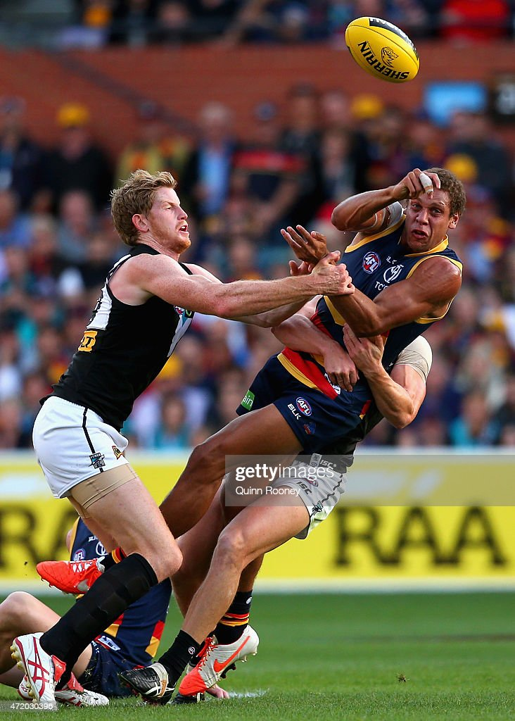 Cam Ellis-Yolmen of the Crows handballs whilst being tackled by Matthew Lobbe and Hamish Hartlett of the Power during the round five AFL match between the Adelaide Crows and the Port Adelaide Power at Adelaide Oval on May 3, 2015 in Adelaide, Australia.