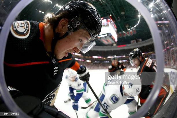 Cam Fowler and Adam Henrique of the Anaheim Ducks battle Alex Biega of the Vancouver Canucks for a loose puck during the first period of a game at...