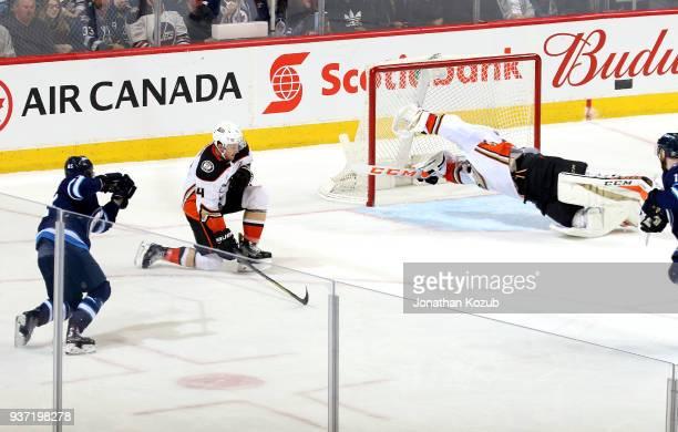 Cam Fowler of the Anaheim Ducks blocks a shot by Mathieu Perreault of the Winnipeg Jets as goaltender John Gibson dives across the crease during...