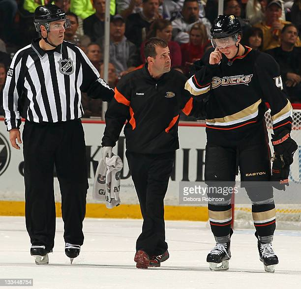 Cam Fowler of the Anaheim Ducks is helped off the ice during the game against the Los Angeles Kings on November 17 2011 at Honda Center in Anaheim...