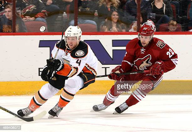Cam Fowler of the Anaheim Ducks passes the puck up ice while being defended by Craig Cunningham of the Arizona Coyotes at Gila River Arena on April...