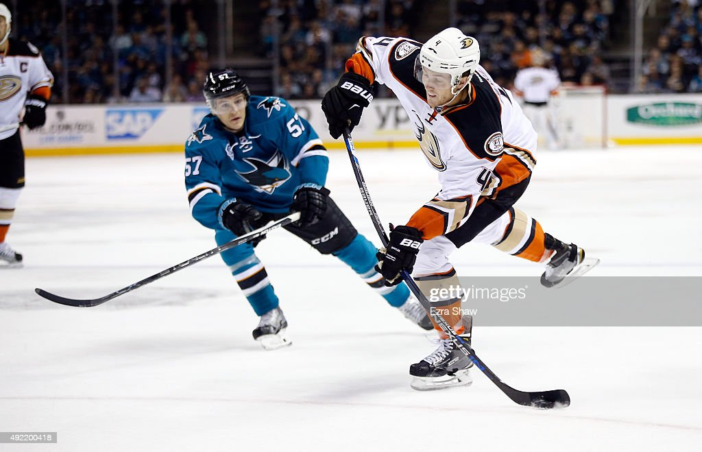 Cam Fowler #4 of the Anaheim Ducks puts a shot on goal while covered by Tommy Wingels #57 of the San Jose Sharks at SAP Center on October 10, 2015 in San Jose, California.