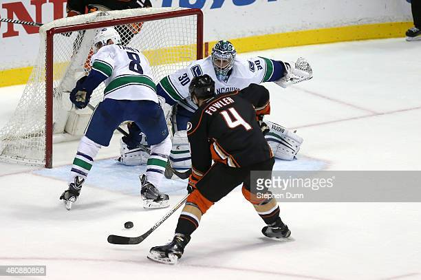Cam Fowler of the Anaheim Ducks shoots and scores the game winning goal in overtime past goalie Ryan Miller and Christopher Tanev of the Vancouver...