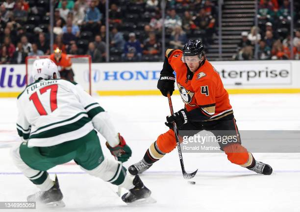 Cam Fowler of the Anaheim Ducks skates the puck against Marcus Foligno of the Minnesota Wild in the first period at Honda Center on October 15, 2021...