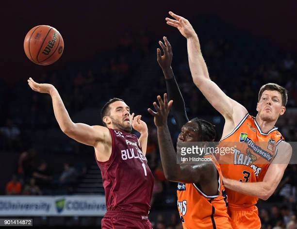 Cam Gliddon and Jerry Evans Jr of the Taipans block a shot from Adam Gibson of the Bullets during the round 13 NBL match between the Cairns Taipans...