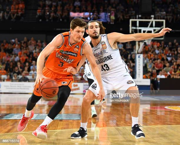 Cam Gliddon of the Taipans drives to the basket past Chris Goulding of Melbourne United during the round nine NBL match between the Cairns Taipans...