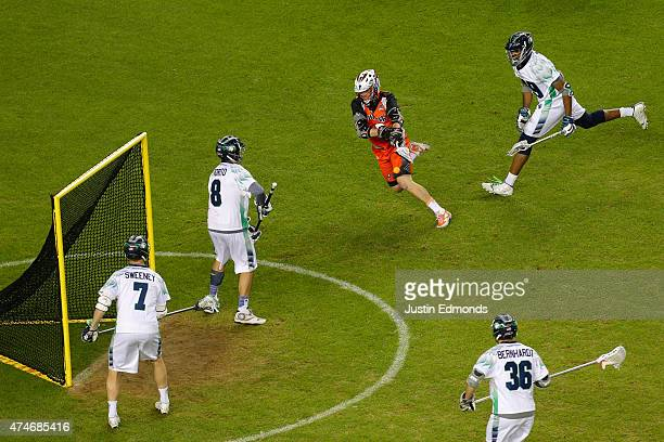 Cam Holding of the Denver Outlaws scores a thirdquarter goal against Tyler Fiorito of the Chesapeake Bayhawks as Kyle Sweeney Mark McNeill and Jesse...