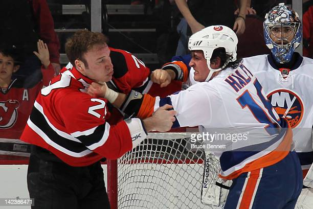Cam Janssen of the New Jersey Devils and Micheal Haley of the New York Islanders fight during the first period at the Prudential Center on April 3...