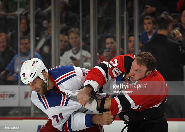 Cam Janssen of the New Jersey Devils and Mike Rupp of the New York Rangers fight just three seconds into the first period at the Prudential Center on...