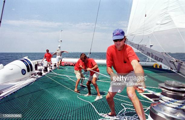 Cam Lewis of the US pulls on a line as he help raise one of the mainsails aboard the 86foot catamaran Explorer 29 May 1999 as he and some of his crew...