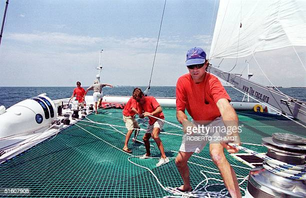 """Cam Lewis of the US pulls on a line as he help raise one of the mainsails aboard the 86-foot catamaran """"Explorer"""" 29 May 1999 as he and some of his..."""