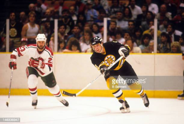 Cam Neely of the Boston Bruins passes the puck as he is pressured by Brude Driver of the New Jersey Devils on February 21 1988 at the Brendan Byrne...