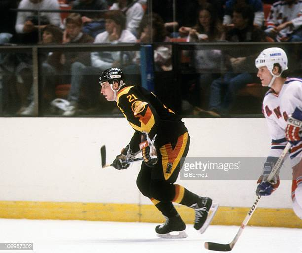 Cam Neely of the Vancouver Canucks skates on the ice as James Patrick of the New York Rangers follows during their game on January 2 1985 at the...