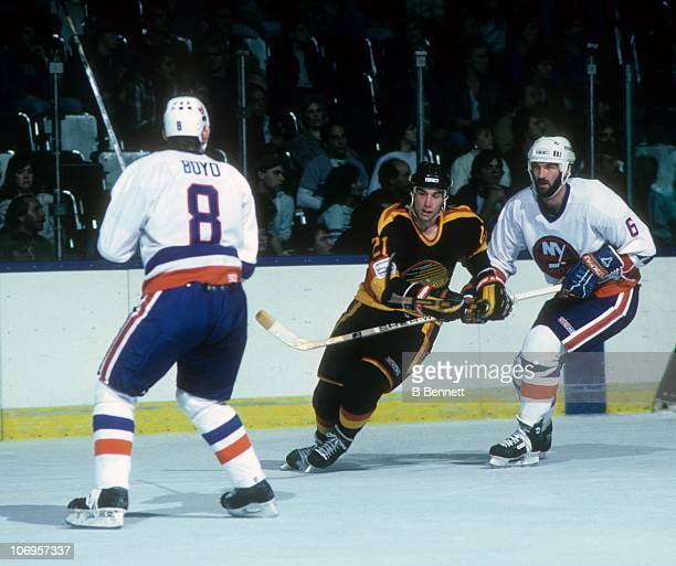 Cam Neely of the Vancouver Canucks skates on the ice as Ken Morrow and Randy Boyd of the New York Islanders defend on October 22 1985 at the Nassau...