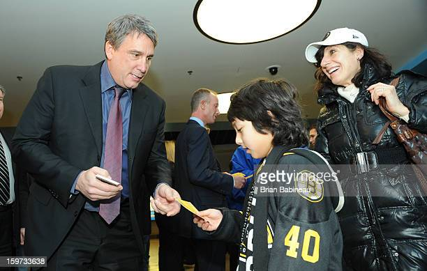 Cam Neely President of the Boston Bruins hands out free concession vouchers to a young fan prior to the game against the New York Rangers at the TD...
